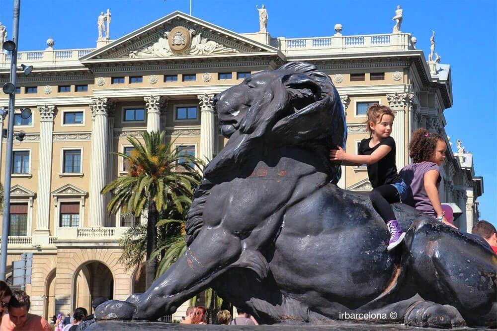 niñas subidas a león junto monumento a Colón
